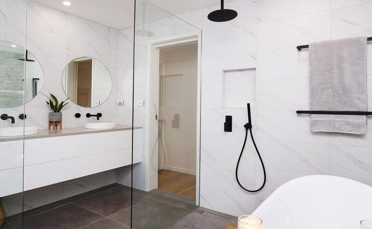 bathroom with two mirror and bathtub with glass divider